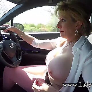 Mature blond damsel Sonia plays with her hooters while driving